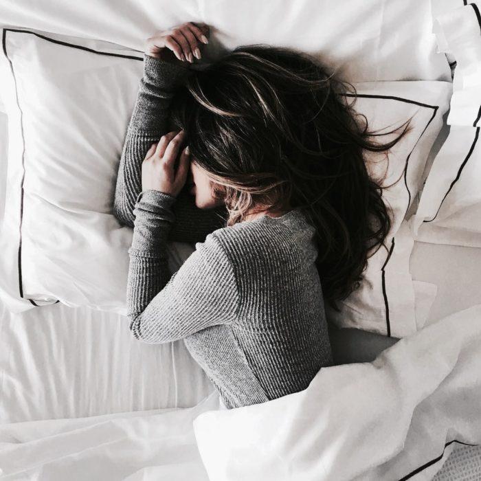 Chica recostada en la cama durmiendo
