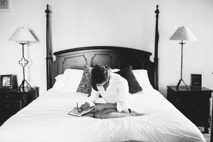 Chica sentada en la cama escribiendo sobre una libreta