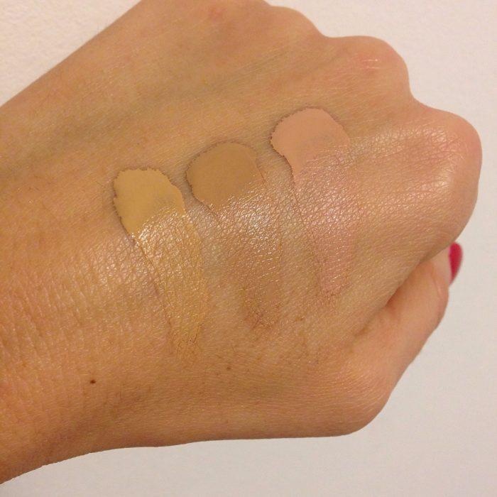 Chica probando la base del maquillaje en la mano