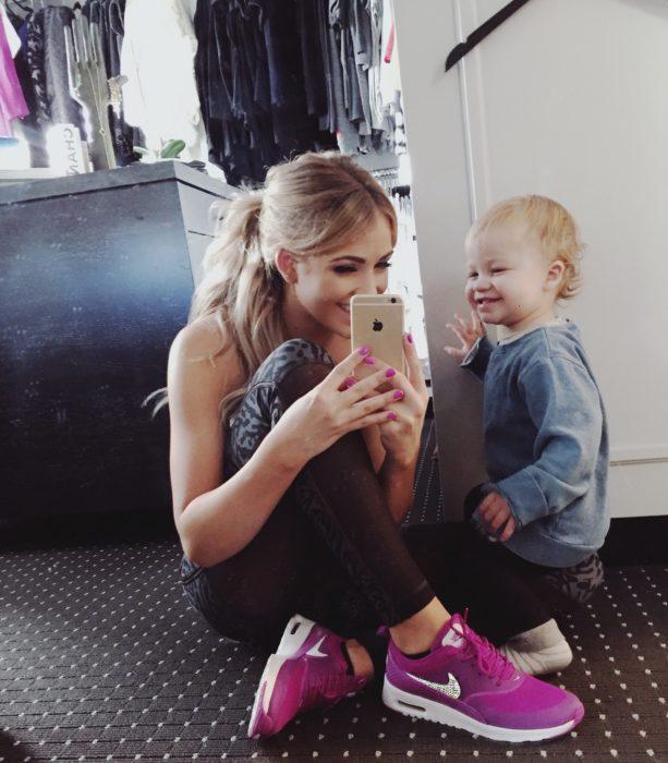 mujer rubia al lado de bebé toman selfie