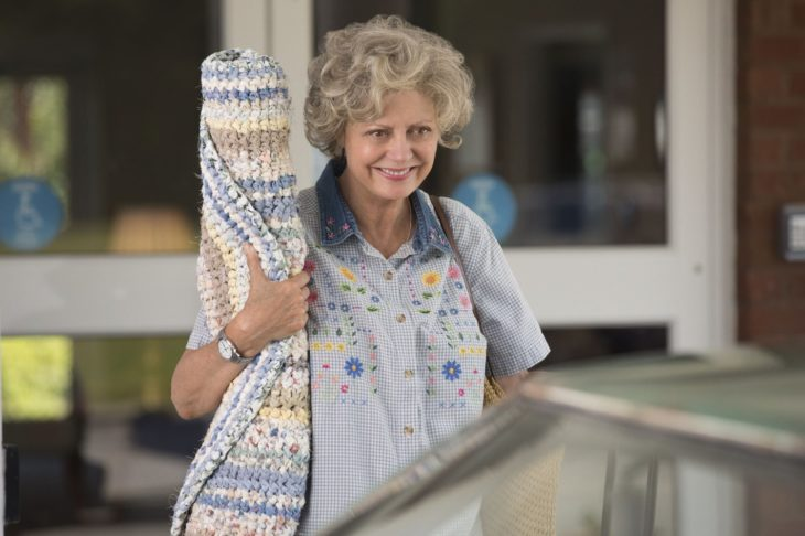 old woman with rolled carpet