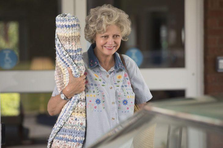 mujer anciana con alfombra enrollada