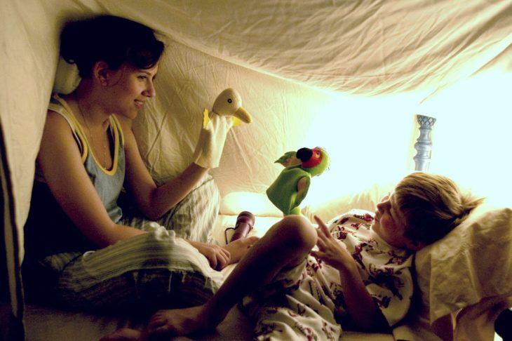 mujer bajo sabana jugando con niño
