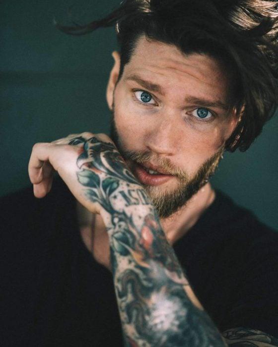 Chico de ojos azules, tatuajes y barba