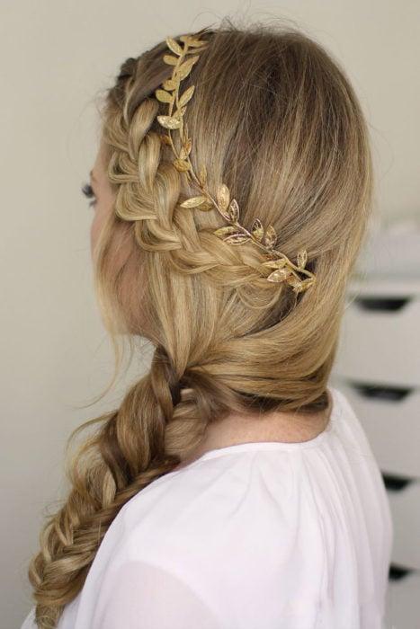 Chica con una trenza de lado y un adorno de hojas en el cabello