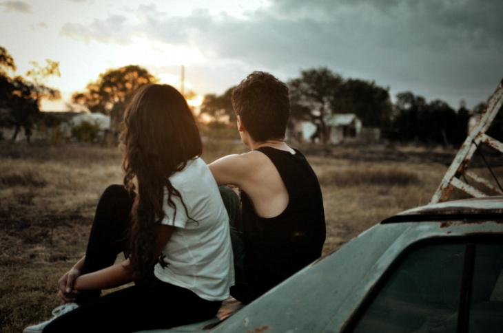 Pareja sentada en un coche viendo al horizonte
