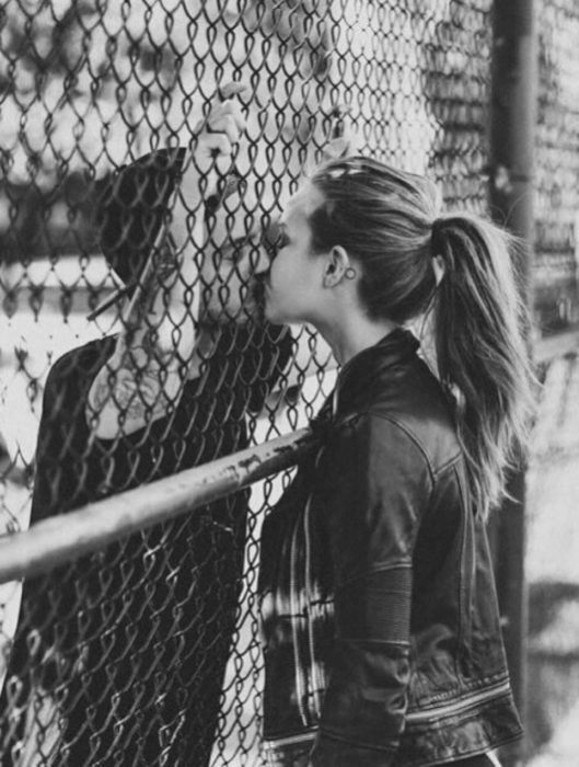 Pareja besándose a través de una reja