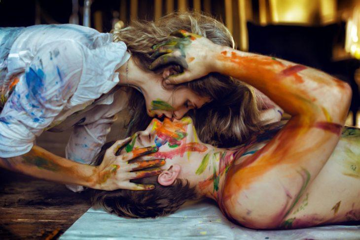 Chicos llenos de pintura besándose
