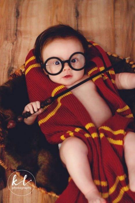 Bebé posando con una varita mágica en una sesión al estilo Harry Potter