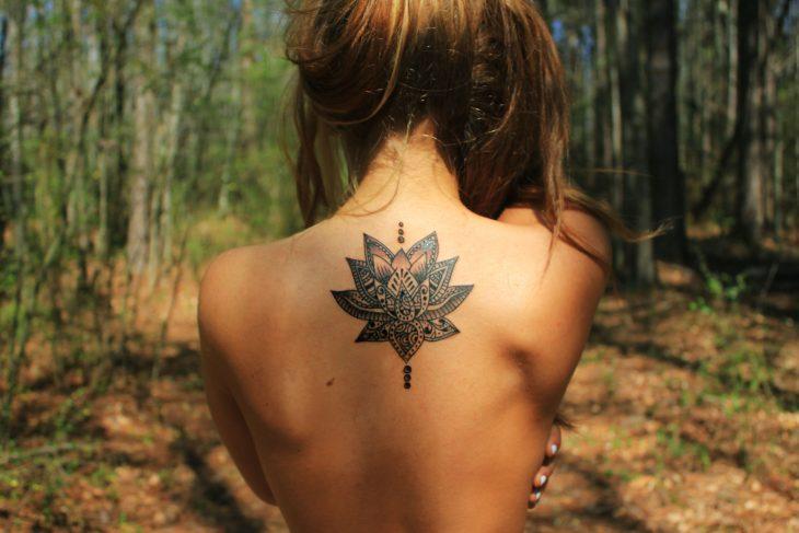mujer de espaldas y tatuaje de flor de loto