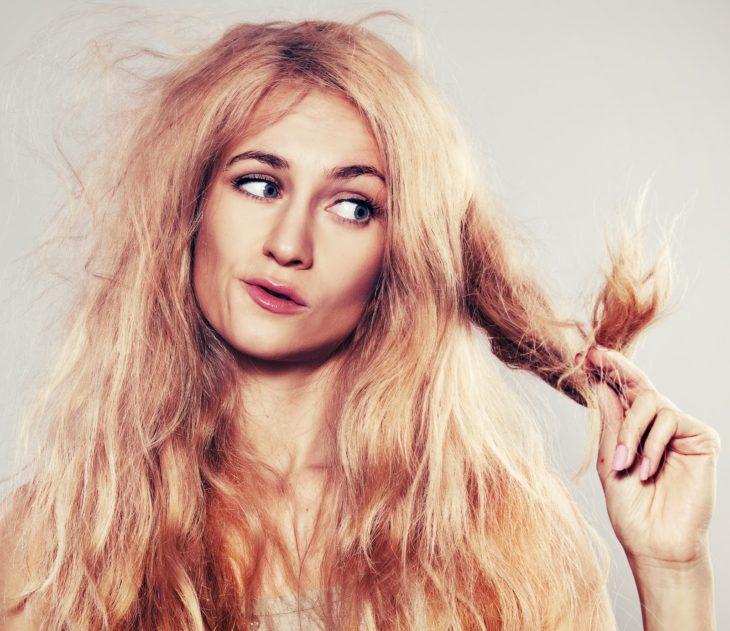 Chica observando las puntas de su cabello
