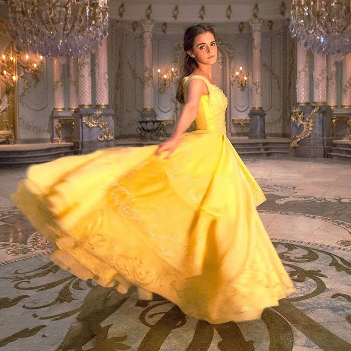 Emma dressed in yellow in the ballroom.