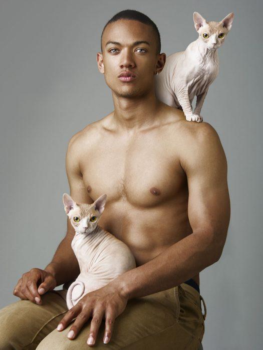 Modelo posando con dos gatos.