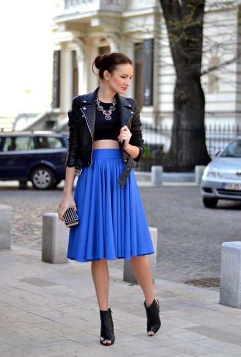 Chica usando una falda tableada en color azul y una chaqueta de cuero