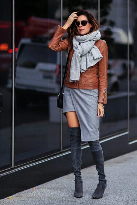 hica usando una falda color gris, botas y chaqueta