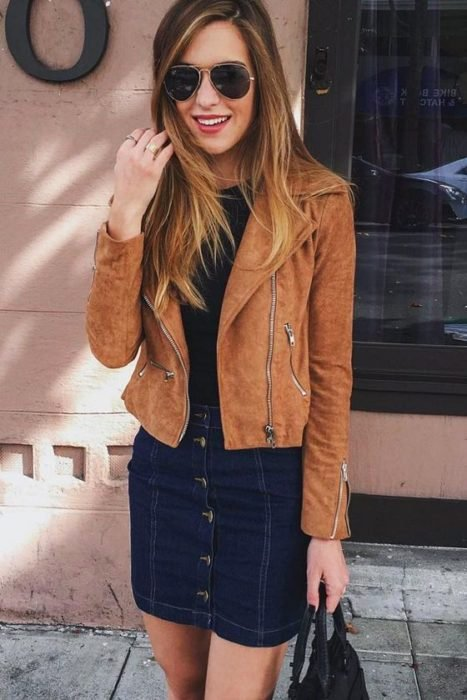chica usando una chaqueta de cuero color café y una falda de mezclilla