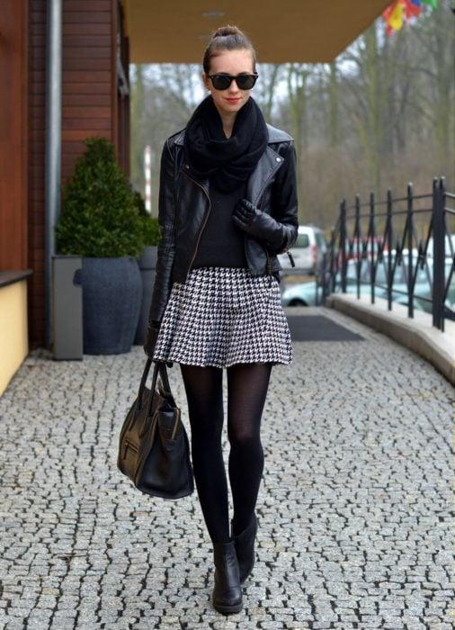 Chica usando una falda escocesa y una chaqueta de cuero negra