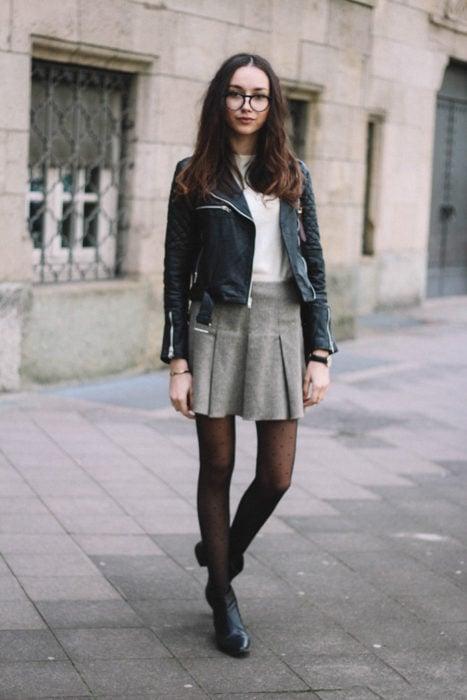 Chica usando una falda gris y una chaqueta de piel