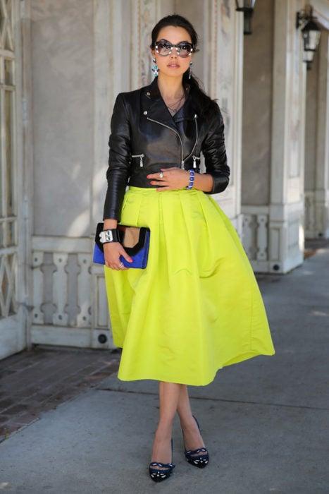Chica usando una falda de color amarillo y una chaqueta de color negro