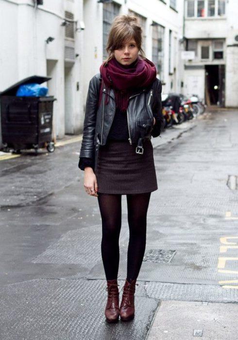 Chica usando una chaqueta de cuero y una falda color guinda