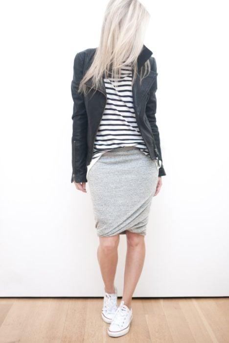 Chica usando una falda gris, blusa rayada y chaqueta de piel