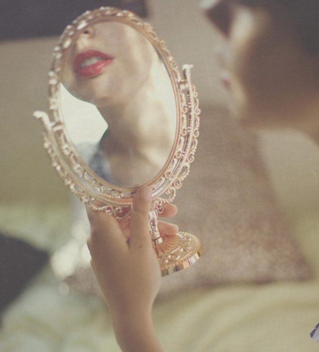 Muchacha mirándose en un espejo.