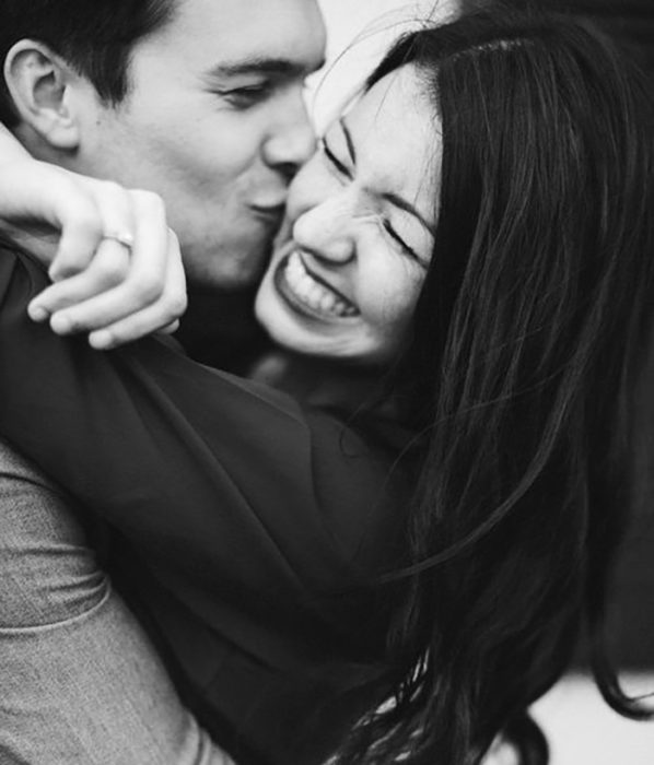 Couple kissing and smiling.