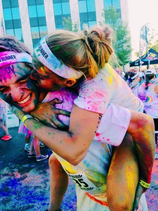 Pareja abrazados y besándose en una carrera de colores.