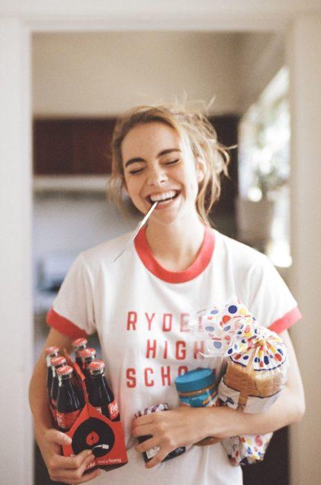 Chica sonriendo con pan y cocas en la mano.