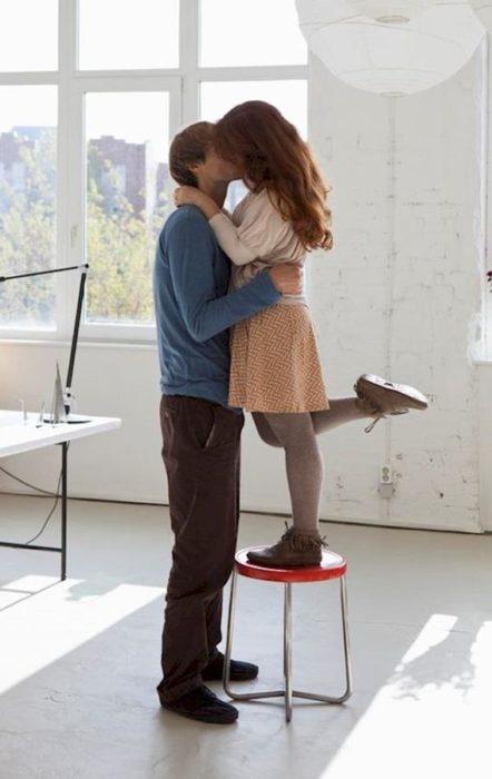 Mujer pequeñas besando a su novio.