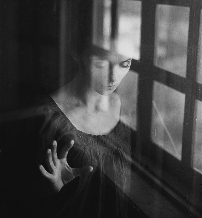 Muchacha mirando a través de una ventana.
