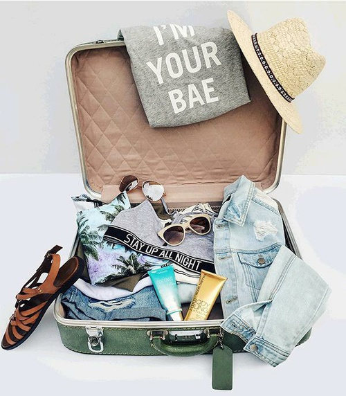 maleta con ropa sandalias y sombrero