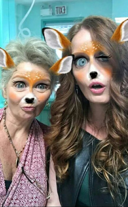 Girl and grandmother using filter deer Snapchat