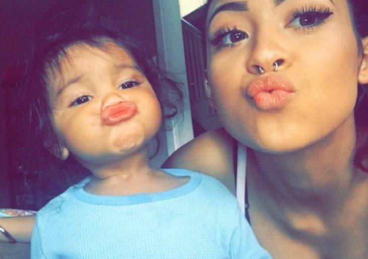 mujer envía beso junto a niña