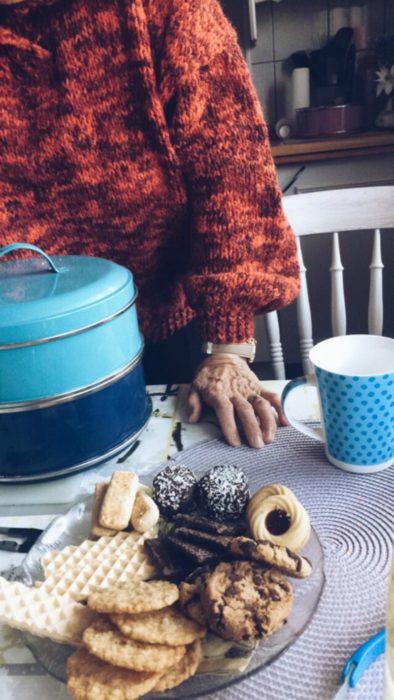 mujer anciana con galletas y café en la mesa