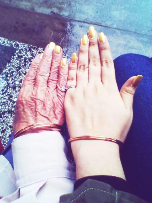 mano de chica con anillo y mano de mujer anciana