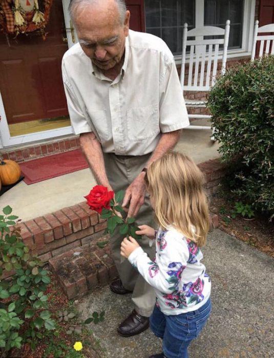 El señor Dan regalándole una rosa a la pequeña.