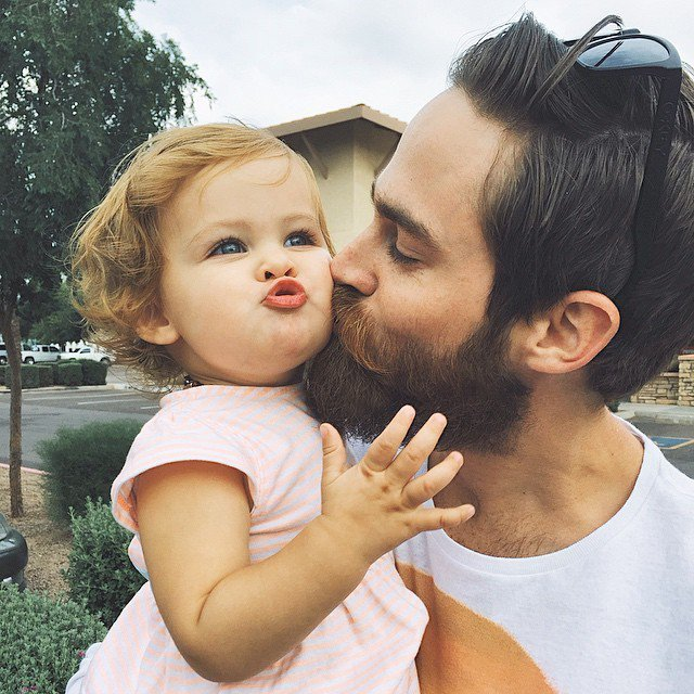Bearded father kissing his daughter.