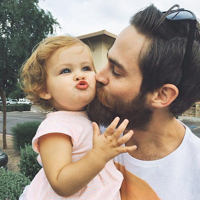 Papá con barba besando a su hija.