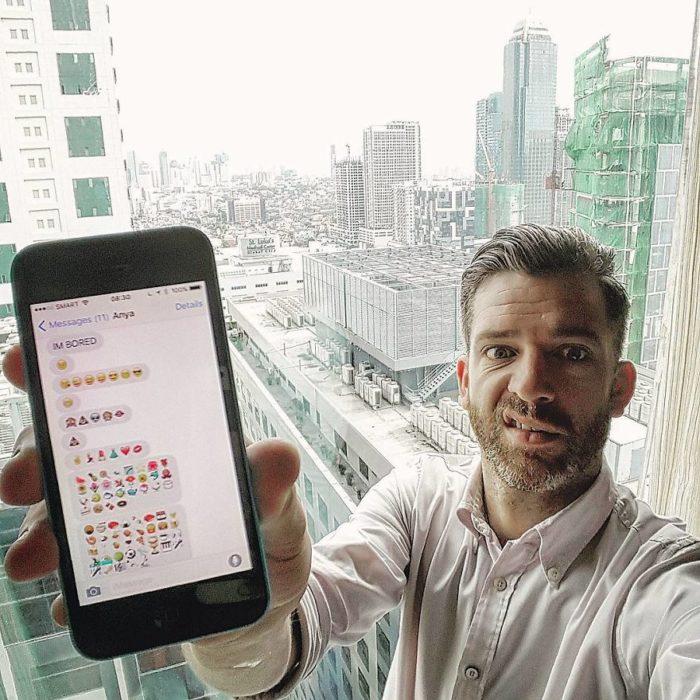 hombre rubio en edificio con celular