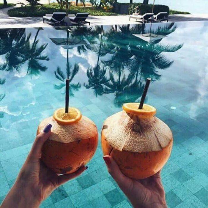 dos manos con cocos y alberca