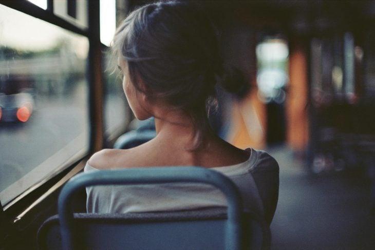 Muchacha mirando por la ventana de un autobús.