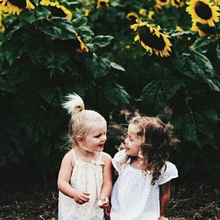 niñas de la mano se miran y sonríen