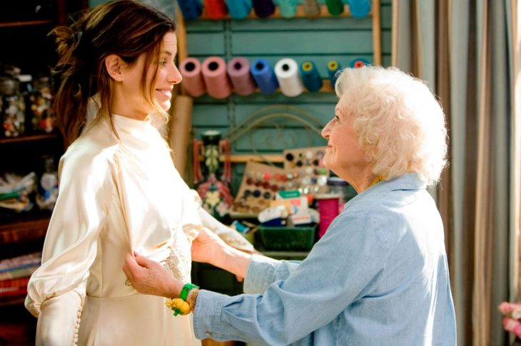 woman with elderly woman trying on clothes