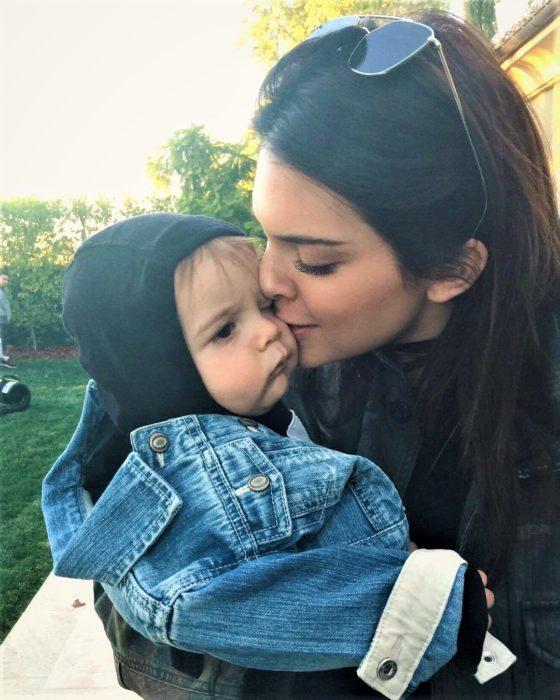 mujer blanca le da beso a niño