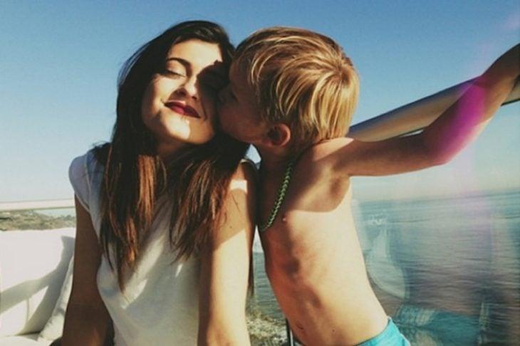 mujer blanca cabello negro y niño da beso