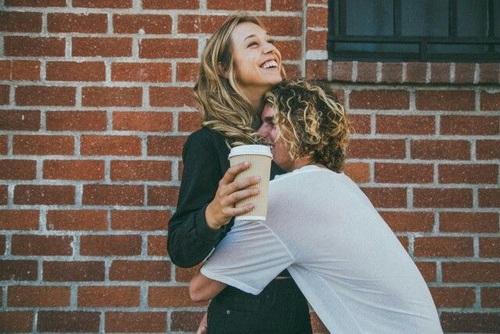 Pareja sonriendo mientras él la abraza a ella.