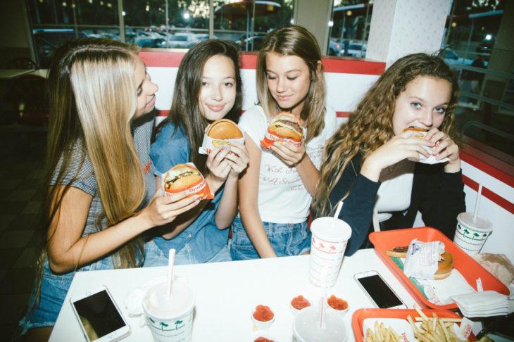 grupo de amigas comiendo pizza por la tarde