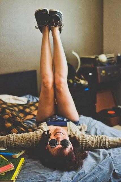 Chica sentada en la cama con los pies hacia arriba