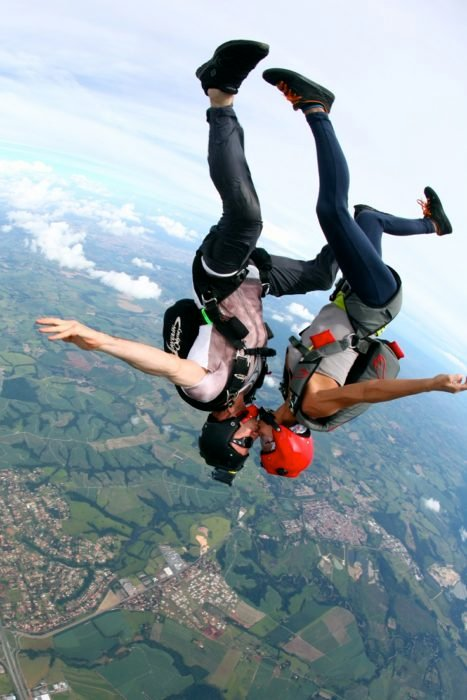 Pareja brincando de un avión con un paracaídas